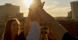 UFG employees giving each other a high five during sunset on top of building