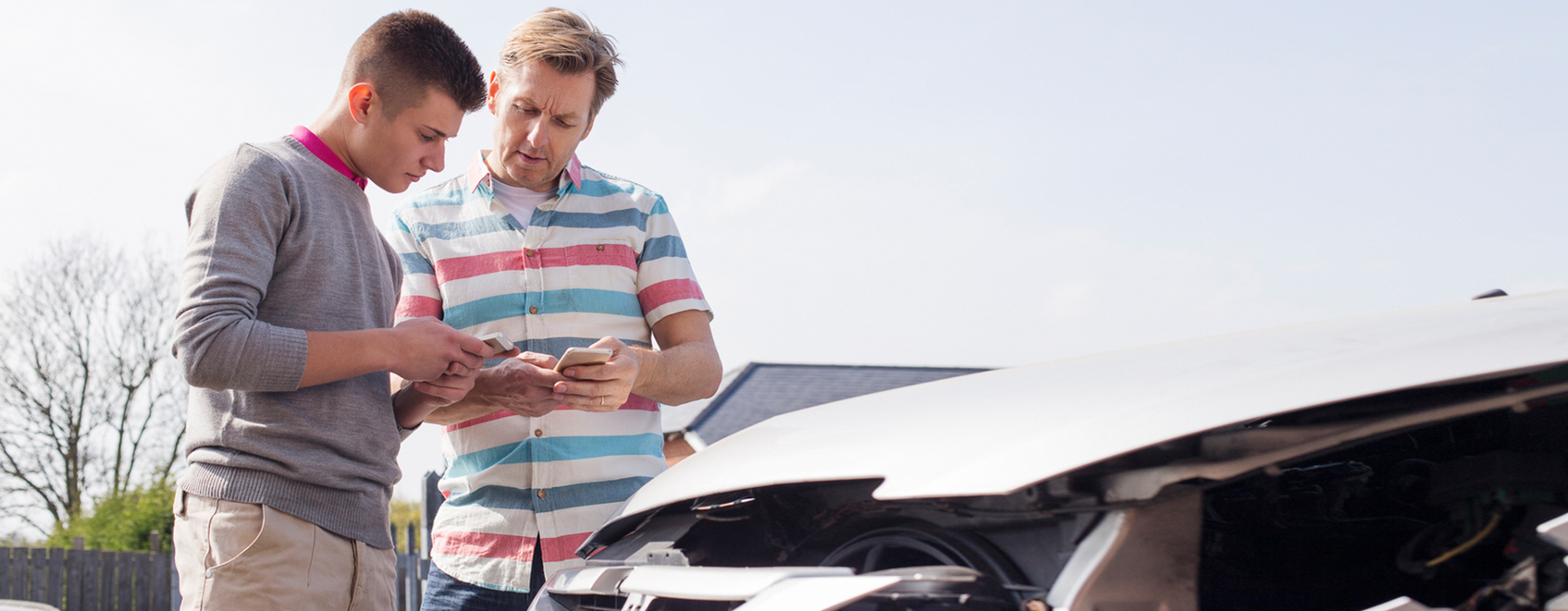 People discussing a car crash while looking at their phone.
