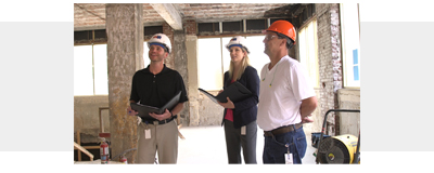 Three people standing and talking in a construction site.