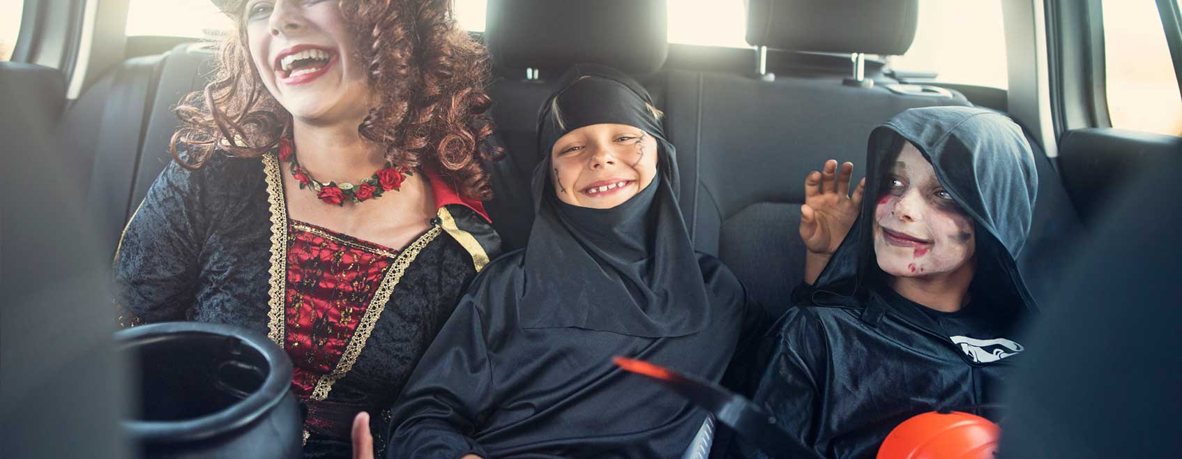 three children in Halloween costumes, laughing in the backseat of a car