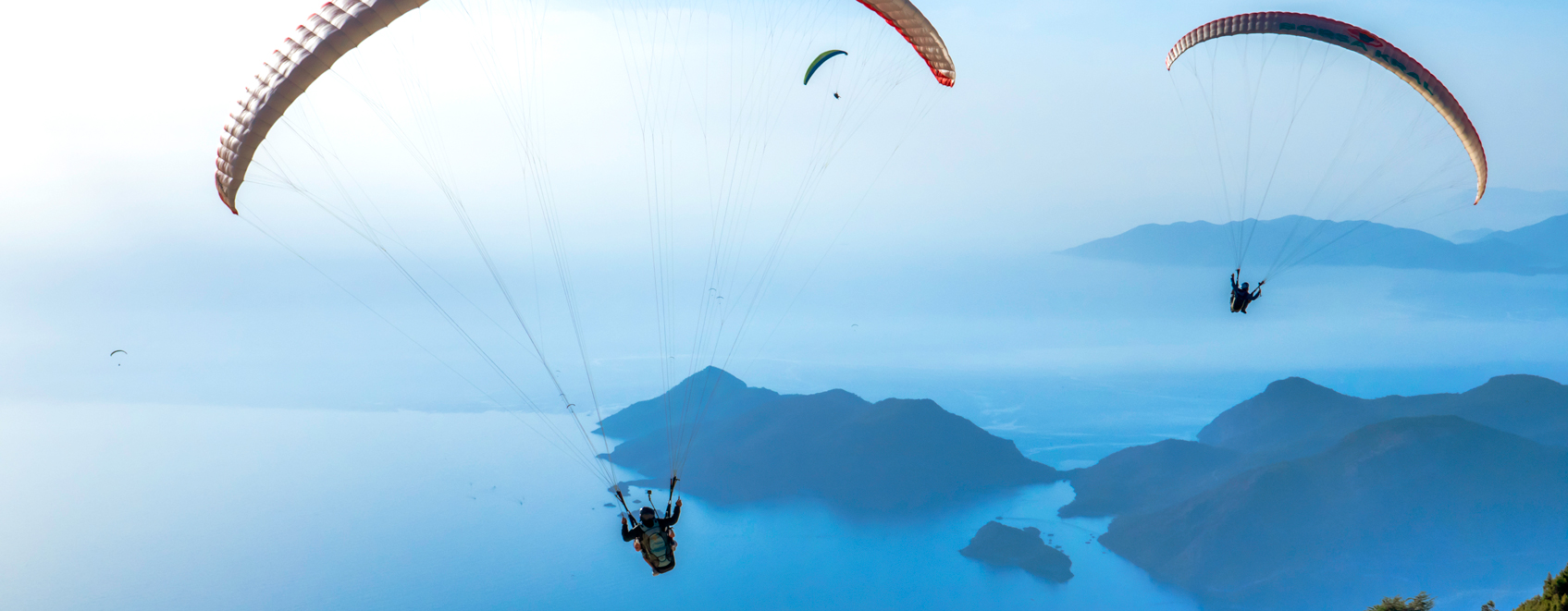 three persons parasailing in sky