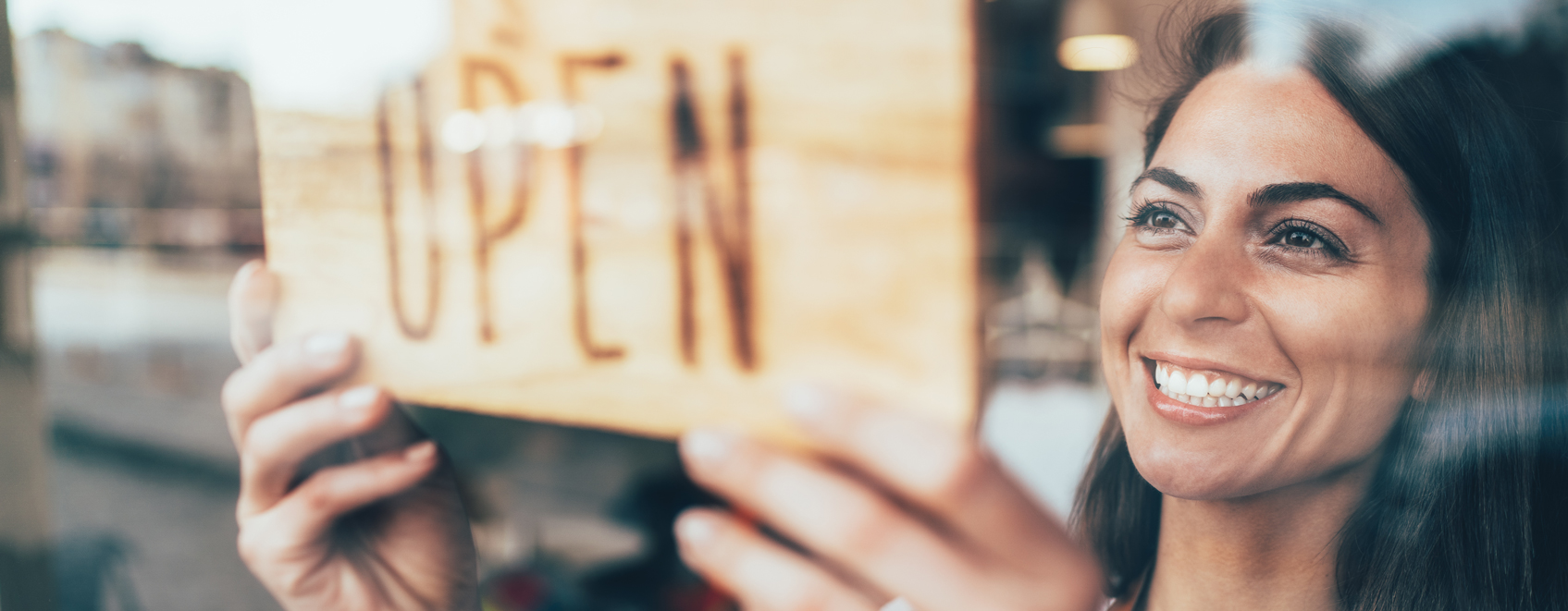 Person in storefront window with 'open' sign.