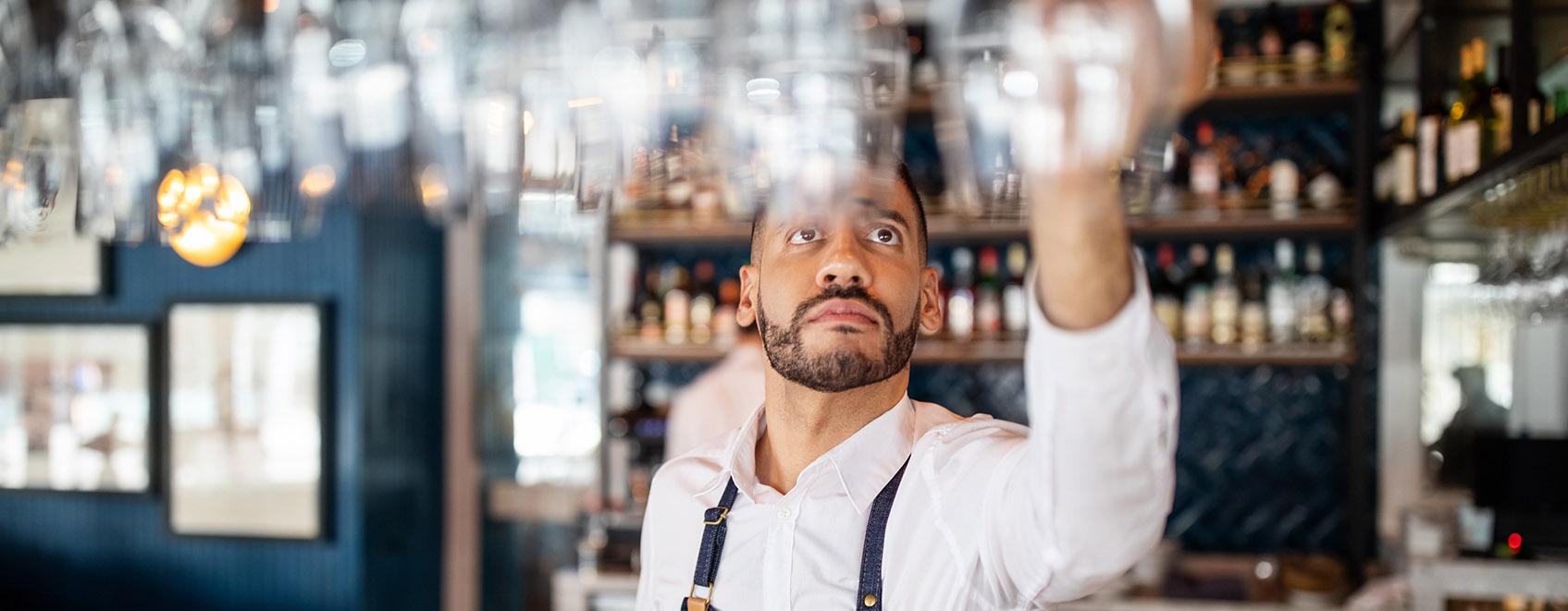 Bartender hanging wine glasses above the bar.