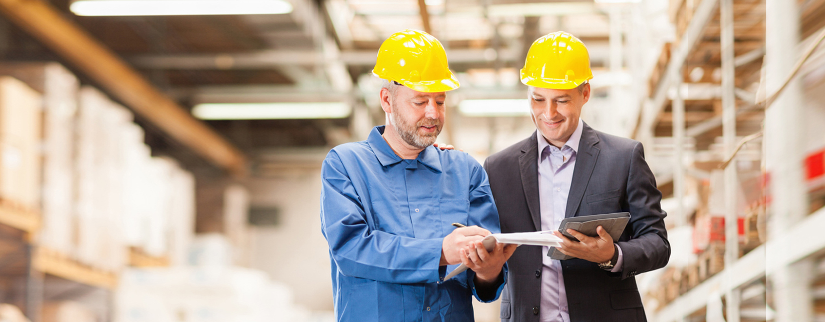 2 people in hardhats, reviewing papers in warehouse