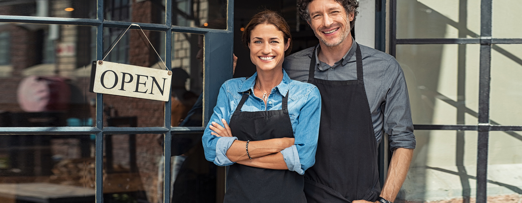 two business owners smiling next to Open sign