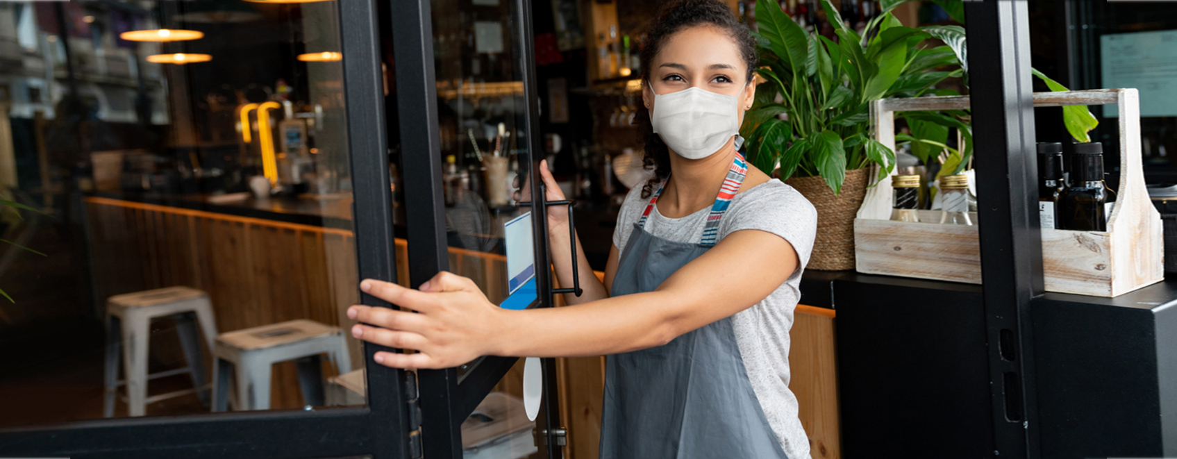 business owner in mask, opening front door of cafe