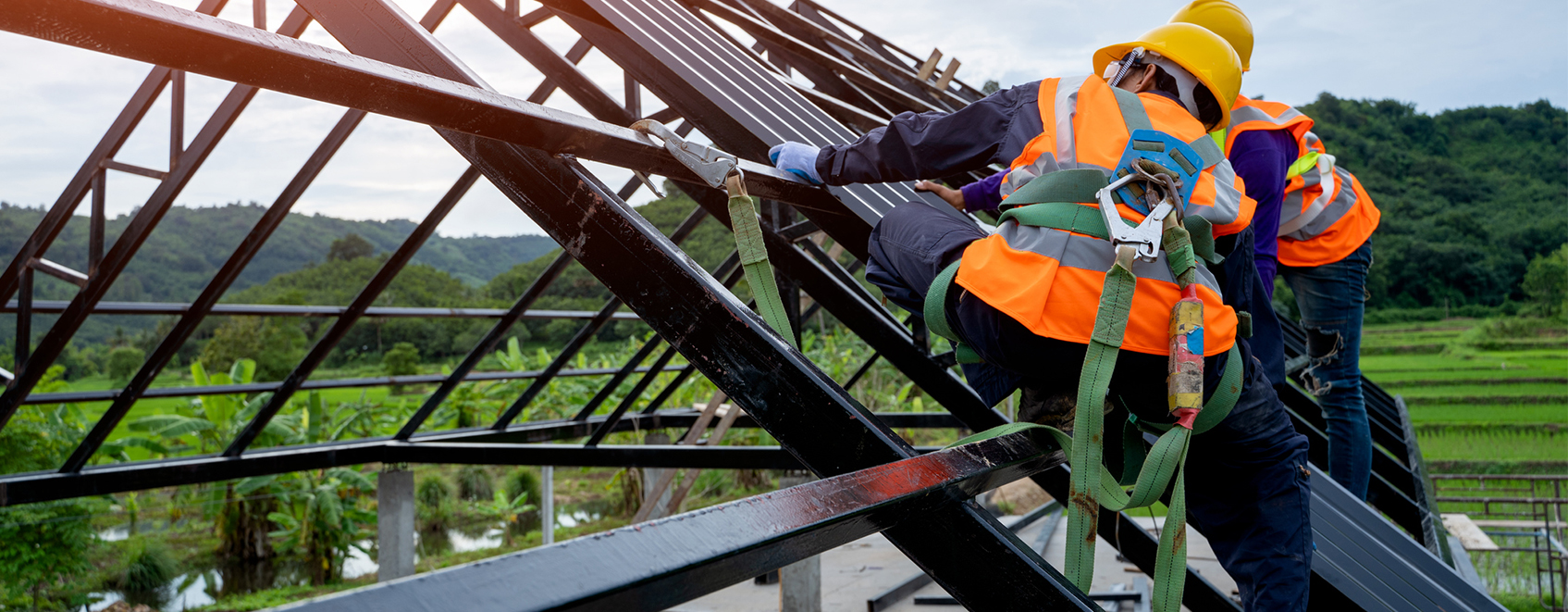 construction workers on roof, with safety harnesses on