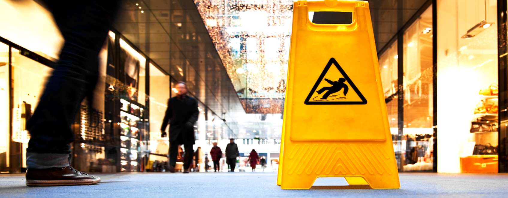 Busy walkway with caution for slippery floors sign.