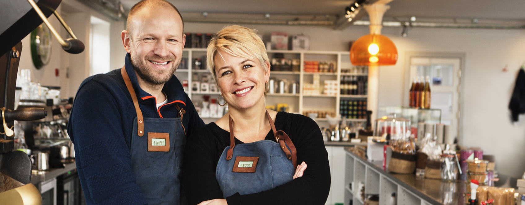 Owners stand smiling in their small business