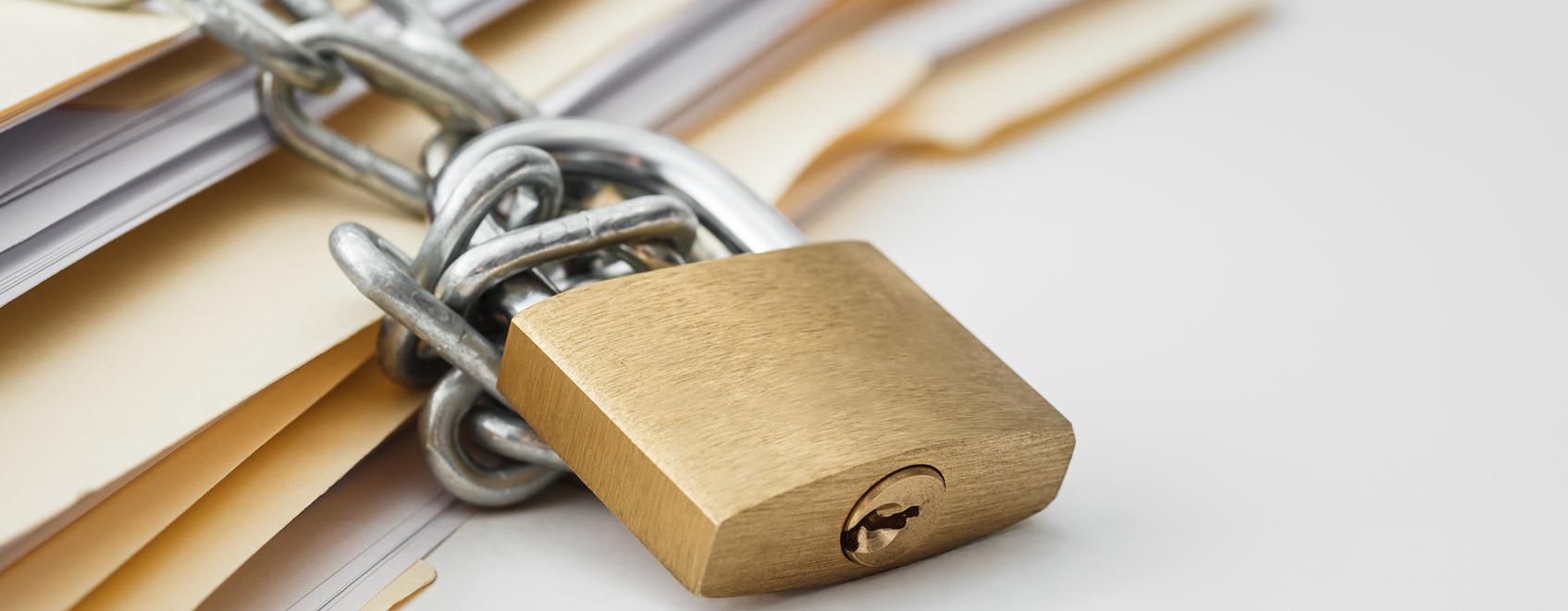 stack of manila folders, with padlock and chains on them