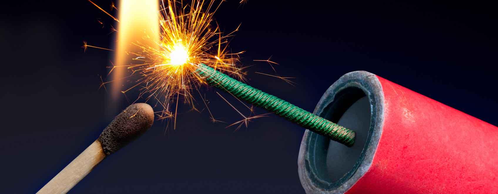 Firecracker being lit by match up close.