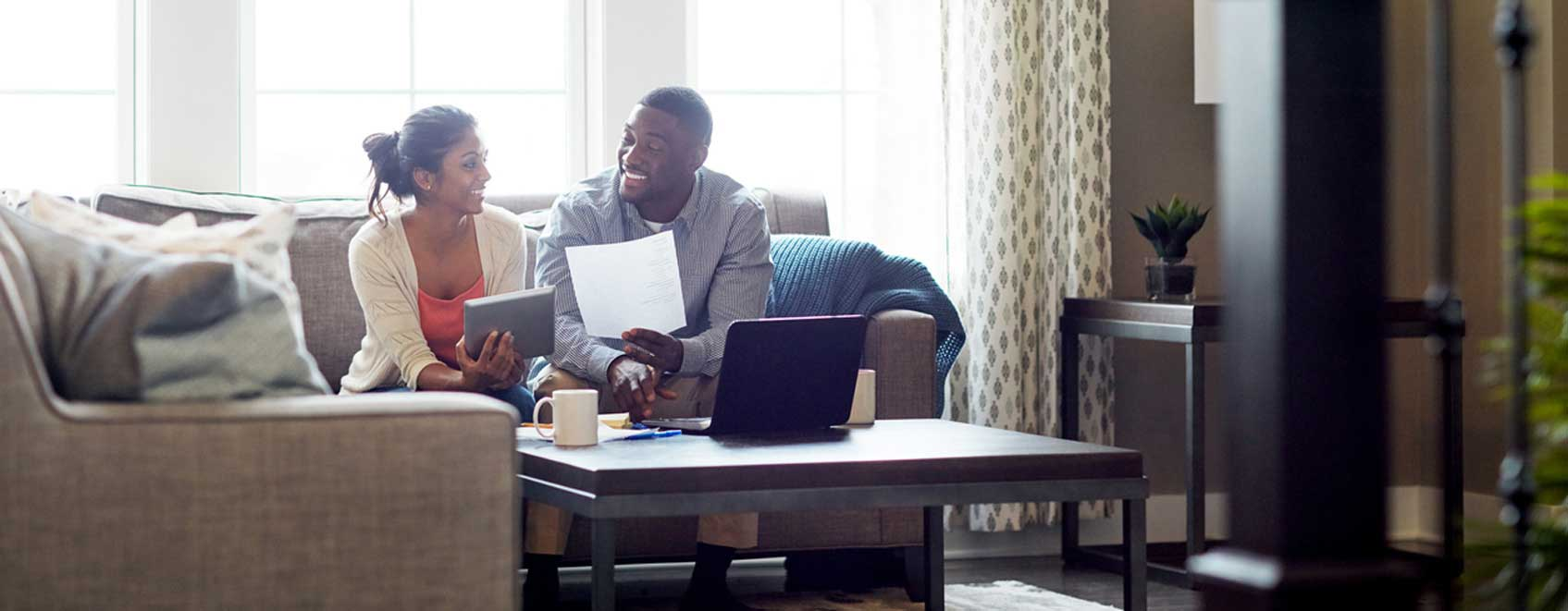 Couple sitting on sofa in their home talking and reviewing homeowners insurance basics.