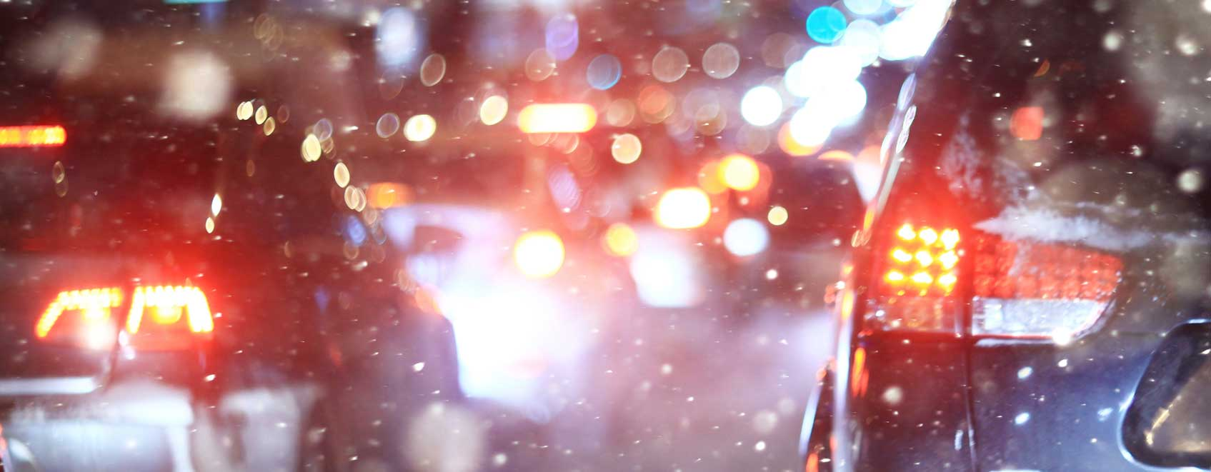 Cars stopped with brake lights on in a night time snow trying not to drive distracted.