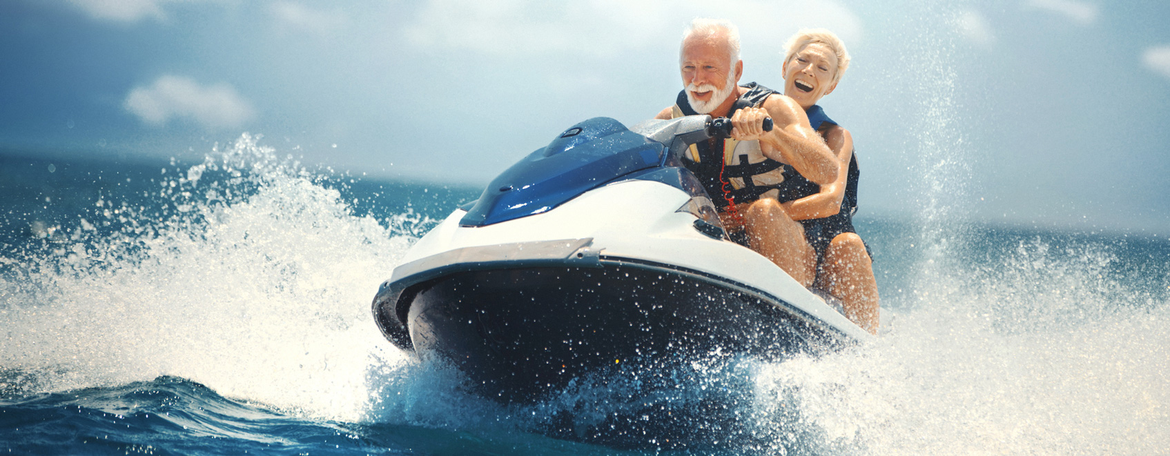 Two people riding on a watercraft enjoying themselves.