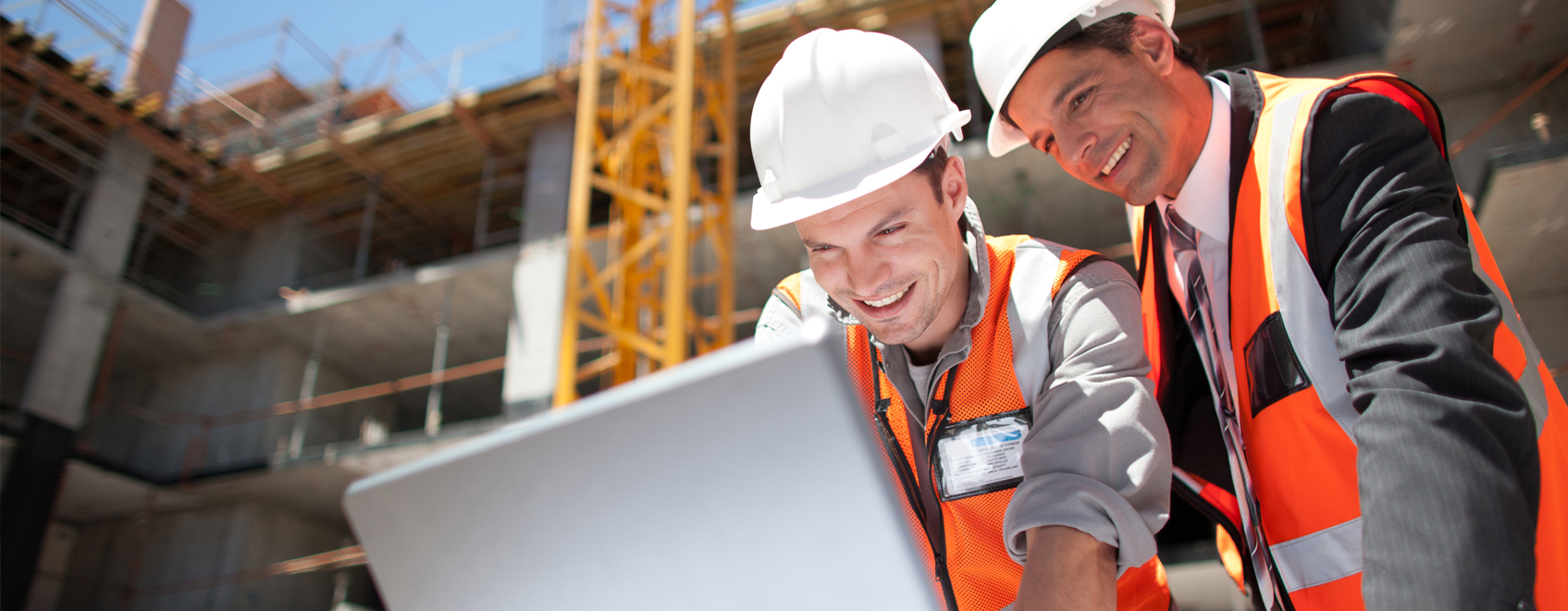 Construction team at work site smiling while looking at laptop together.