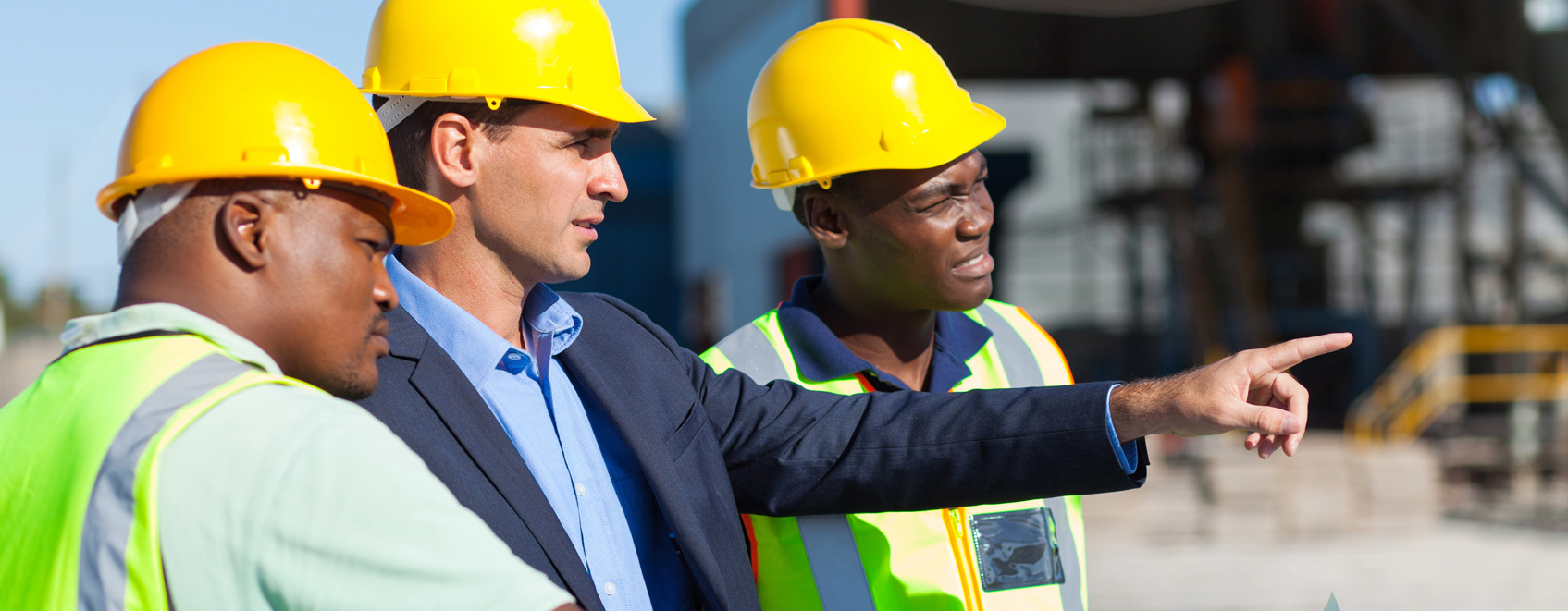 Three people in hard hats at construction site with the leader pointing out good work.