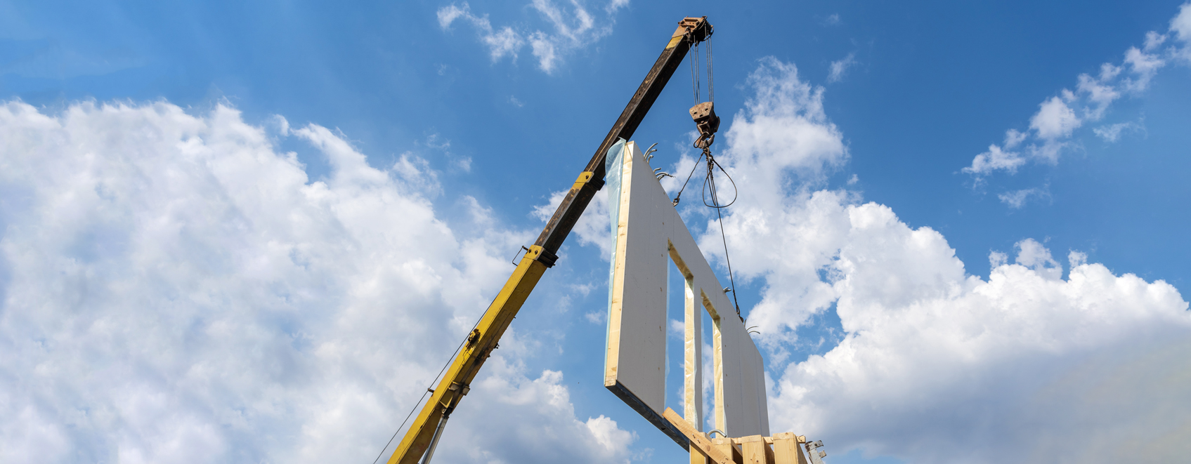 Crane moving walls at pre-fab construction facility