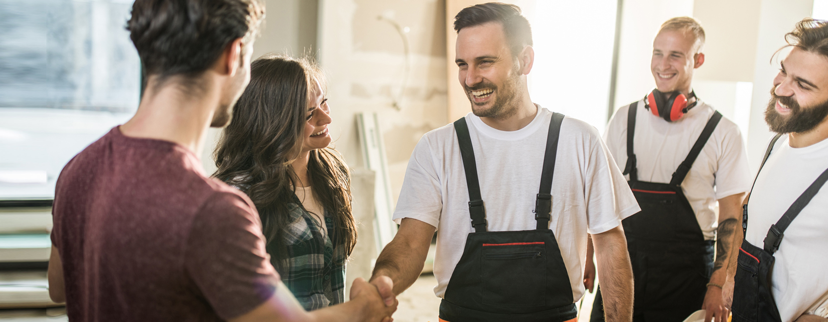 Contractors shaking hands with local business owners in-between work