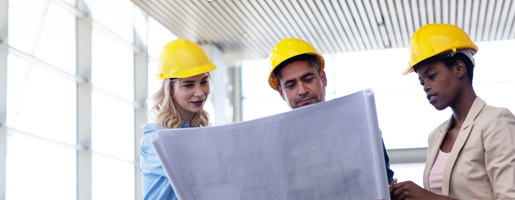 Three people in hard hats reviewing construction blueprints.
